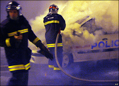 Firemen try to extinguish a burning police car hit by a Molotov cocktail in Villiers-le-Bel