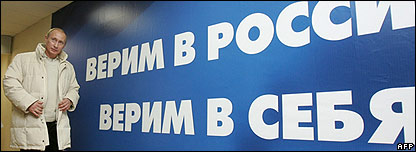 President Vladimir Putin next to poster reading: We believe in Russia, we believe in ourselves