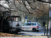 A police car drives past a burnt-out lorry in Villiers-le-Bel, 27 November 2007