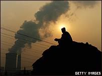 Campesino frente a la chimenea de una fábrica