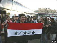 An Iraqi refugee holds his national flag before refugees board buses to return to Iraq from Damascus (27/11/2007)