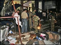 Sri Lankan soldiers and firefighters search through wreckage outside a shop in Colombo