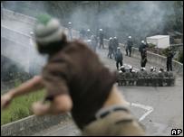 Estudiante universitario lanza piedras a la polic�a durante protesta contra el proyecto de reforma constitucional