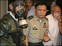 Renegade soldier Brig Gen Danilo Lim, centre, is led out of the hotel by police in Manila on 29 November 2007