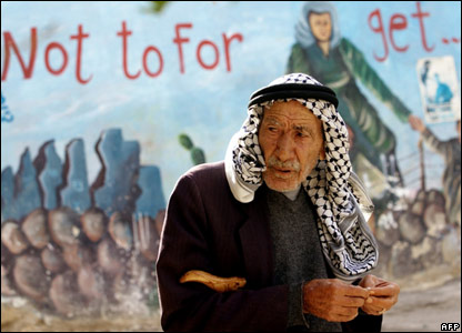 Elderly Palestinian man and mural, Jenin, West Bank.