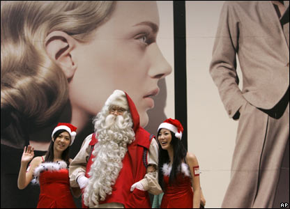 Father Christmas from Finland appears with two models in Hong Kong.