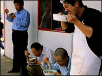 Chinese migrant workers eating in a compound in Angola (Picture by Kate Eshelby)