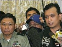 Brigadier General Danilo Lim (L) looks on while Antonio Trillanes (R) announces their surrender