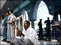 Sudanese reporter smokes a cigarette as he sits outside the Khartoum court, Sudan (29/11/2007)