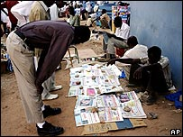 Sudanese read newspapers at a street vender's corner outside the Khartoum court (29/11/2007)