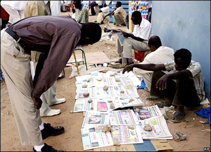 A Sudanese man reads newspapers at a street vender's corner outside the Khartoum court