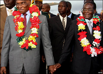 Senegal's President Abdoulaye Wade (l) holds hands with Zimbabwe's President Robert Mugabe (r)