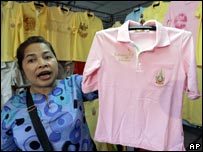 Thai woman holds up a pink shirt