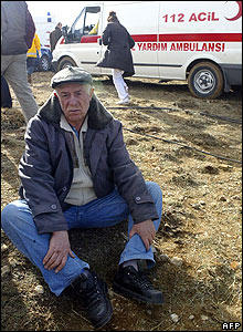 Relative of crash victim sits on ground at crash site near Keciborlu, in Isparta province, Turkey.