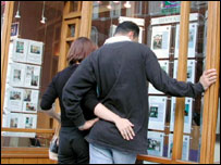 Couple looking in to an estate agent's window