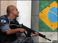 An armed police man crouches by a Brazil flag mural (28/06/2007)