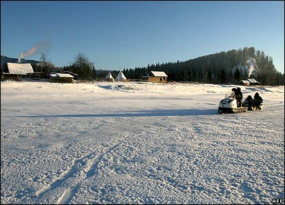 Members of an electoral voting commission drive a snowmobile to villagers in the remote Siberian village of Shor-Taiga