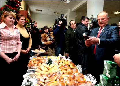 Leader of the Communist party Gennady Zyuganov looks at refreshments on sale at a polling station in Moscow.