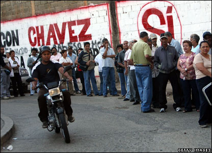 Voters line up in front of pro-Chavez graffiti at a polling station in Petare, Caracas (02/12)
