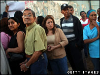 Voters line up before casting their ballots at a polling station in Petare, Caracas