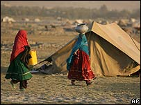 Afghan women leave their tents to bring water on the outskirts of Kabul