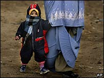 An Afghan boy in Kabul holds his mother's hand
