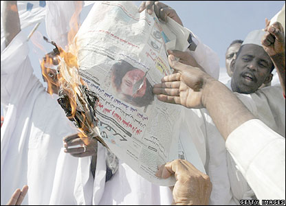 Sudanese demonstrators burn a newspaper bearing the photo of Gillian Gibbons