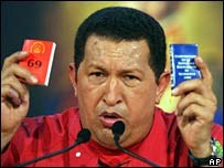 Hugo Chavez holds a copy of the constitution and the proposed reforms