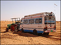 Manon Ossevoort's tractor hauls a stranded bus through the desert