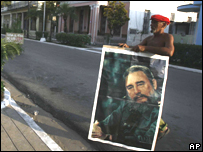 Un cubano carga un afiche de Fidel Castro