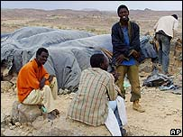 Liberian migrants sit next to their shelters on the edge of Tamanrasset, southern Algeria