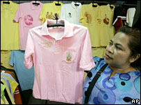 A Bangkok resident holds up one of the pink shirts people have been wearing to support the king