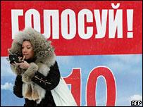 """Девушка красится у плаката """"Единой России"""""""
