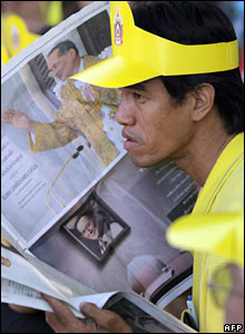 A Thai man reads a local newspaper with pictures of King Bhumibol Adulyadej
