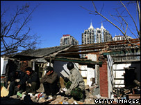 Chinese men sit next to a building demolished to make way for a development for the 2008 Beijing Olympics (4 December 2007)