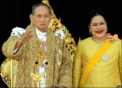 King Bhumibol with Queen Sirikit Adulyadej, with Queen Sirikit, waves to crowds in Bangkok