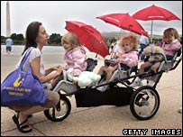 Mother with toddler triplets in a triple buggy