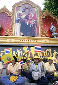 Thai people wave the national flag in front of a portrait of the King and Queen in Bangkok (05/12/2007)