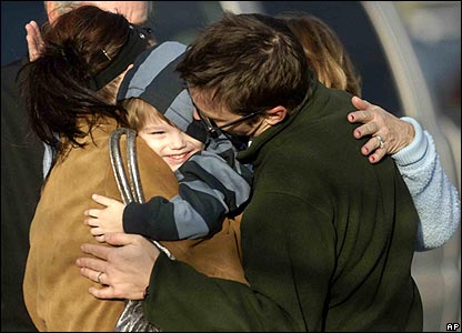 Boy being hugged by family