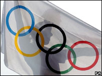 Man holds up Olympic flag