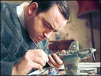 Craig Cash as Malcolm in Mrs Merton and Malcolm. Malcolm is shown painting an Airfix plane.