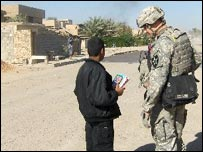 Lieutenant Jake Carisle, 2nd Platoon commander, talks to an Iraqi youth on his way to school in Doura, southern Baghdad