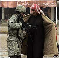 A US soldier frisks an Iraqi man in Baquba, 7 December 2007