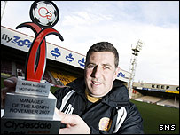 Motherwell manager Mark McGhee shows off his award