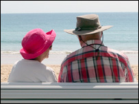 An older couple sitting on a bench by a beach