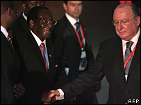 Robert Mugabe is greeted by an official at a reception for the EU-Africa summit, 7 December 2007