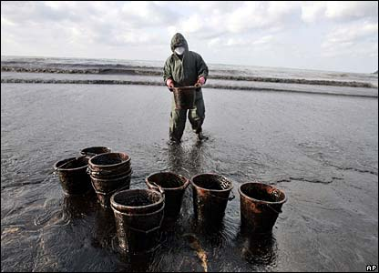 Emergency worker collecting oil in baskets