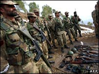 Pakistan troops with weapons they say were seized from the militants