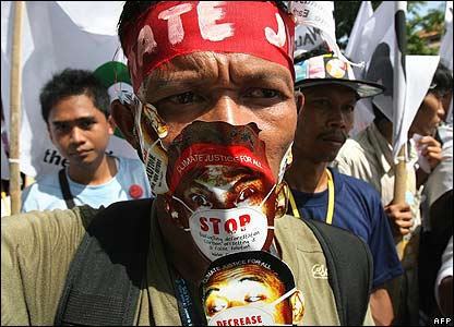 An environmental activist poses with a placard during a protest in Denpasar, on Bali island