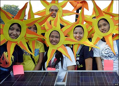 Climate change activists in the Philippines stand beside solar panels to raise awareness of solar energy